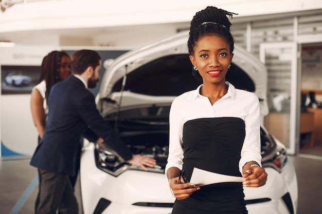 Dos mujeres negras con estilo en un salón de autos Foto gratis