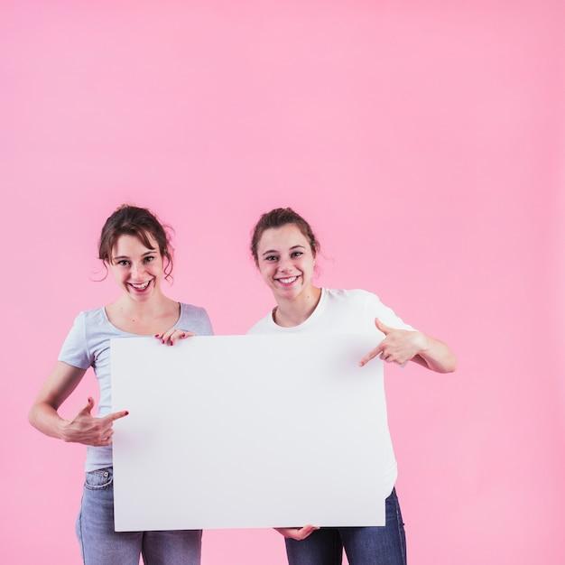Dos mujeres que señalan el dedo sobre el cartel en blanco que se opone al contexto rosado Foto gratis
