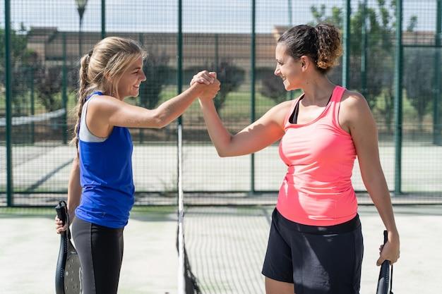 Dos mujeres en ropa deportiva tomados de la mano con una expresión de satisfacción en una cancha de tenis Foto Premium