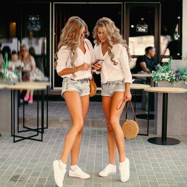 Dos mujeres seductoras que pasan tiempo juntas, usando un teléfono inteligente Foto Premium