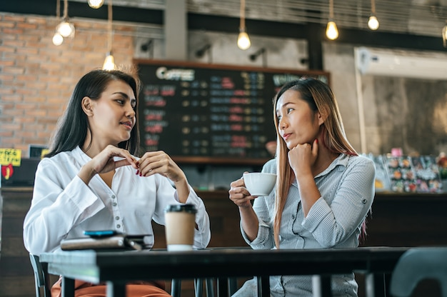 Dos mujeres sentadas y tomando café y charlando en una cafetería Foto gratis