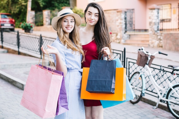 Dos mujeres sonrientes con bolsas de papel Foto gratis