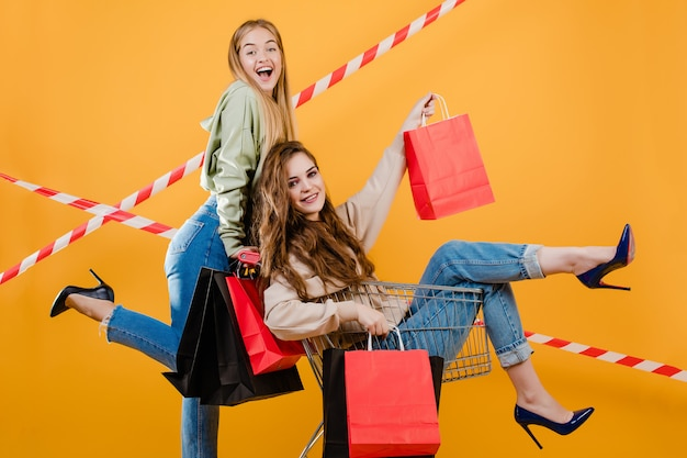 Dos mujeres sonrientes felices tienen carro con coloridos bolsos de compras y cinta de señal aislada sobre amarillo Foto Premium