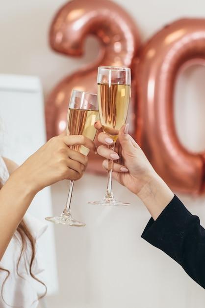 Dos mujeres tintinean los vasos durante las vacaciones. las manos de cerca. celebracion. Foto Premium