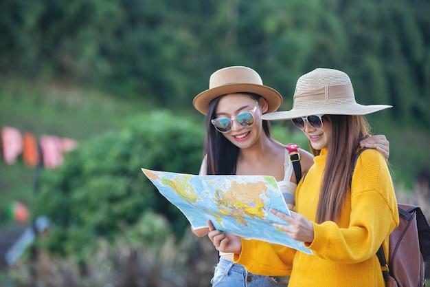 Dos mujeres turistas sostienen un mapa para encontrar lugares. Foto gratis