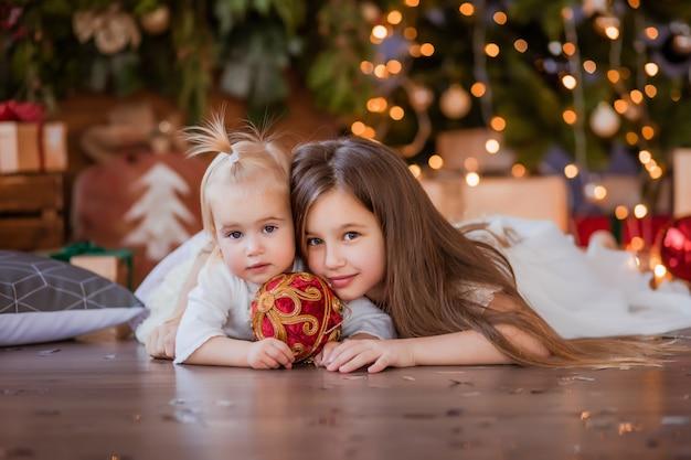 Dos niñas al lado del árbol de navidad Foto Premium