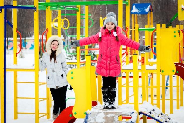 Dos niñas felices, madre e hija jugando en un patio de recreo en el día helado de invierno. Foto Premium