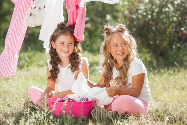 Dos niñas lavandas. hermanas haciendo quehaceres domésticos Foto Premium