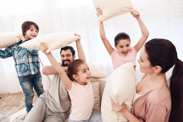 Dos niñas y un niño pelean con almohadas con sus padres. Foto Premium
