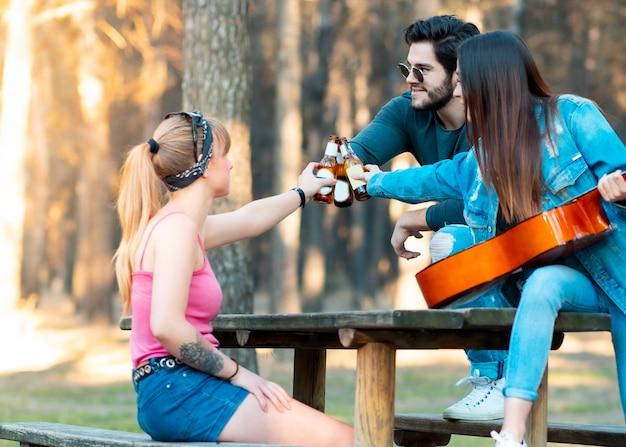 Dos niñas y un niño con vasos de cerveza tocan la guitarra en la naturaleza Foto Premium