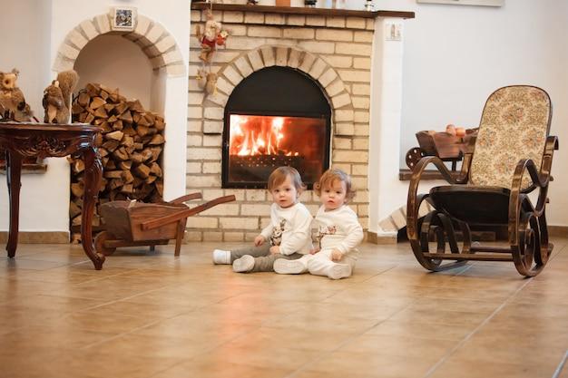 Las dos niñas sentadas en casa contra la chimenea. Foto gratis