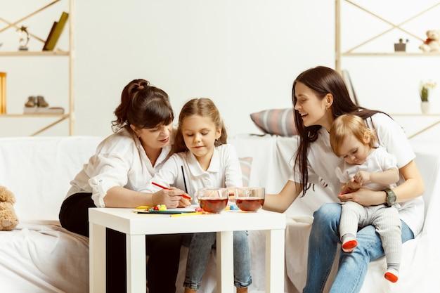 Dos niñas, su atractiva madre joven y su encantadora abuela sentados en el sofá y pasar tiempo juntos en casa. generación de mujeres. día internacional de la mujer. feliz día de la madre. Foto gratis
