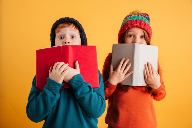 Dos niños pelirrojos asustados cubriéndose los rostros con libros. Foto gratis