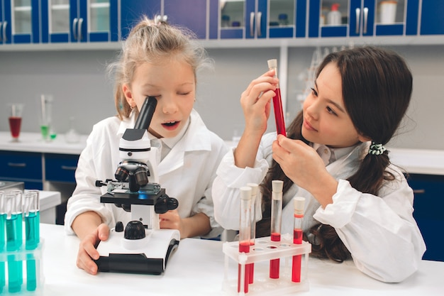Dos niños pequeños en bata de laboratorio que aprenden química en laboratorio de la escuela. jóvenes científicos en gafas protectoras haciendo experimentos en laboratorio o gabinete químico. mirando a través del microscopio Foto Premium