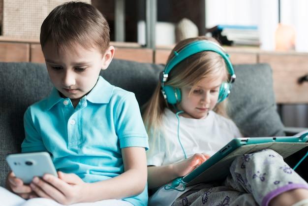 Dos niños con tablet y smartphone Foto gratis