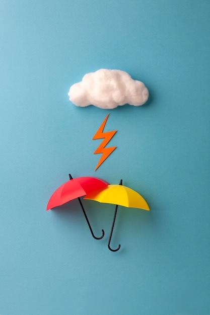 Dos paraguas bajo la nube sobre fondo azul cielo Foto Premium