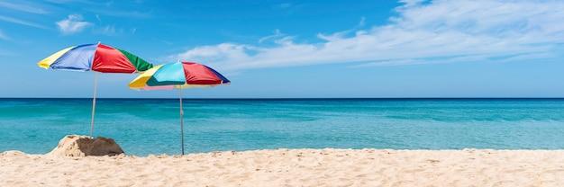 Dos paraguas en la playa tropical. banner de vacaciones de verano Foto Premium
