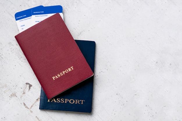 Dos pasaportes de viajeros rojo y azul con tarjetas de embarque para el avión. Foto Premium