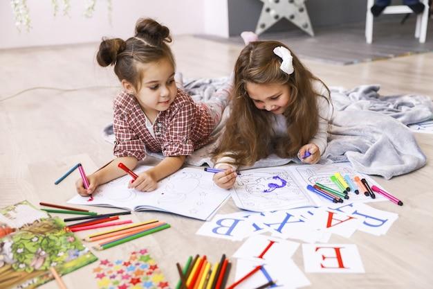 Dos pequeñas muchachas felices que dibujan en el libro para colorear tirado en el suelo sobre la manta y aprendiendo letras Foto gratis