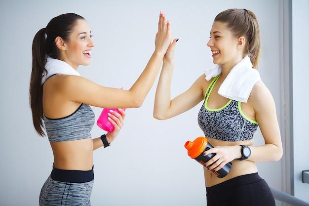 Dos personas que aman el ejercicio están de pie con una mano en posición y abrazándose con otra mano con una sonrisa. es una escena linda y adorable. Foto Premium