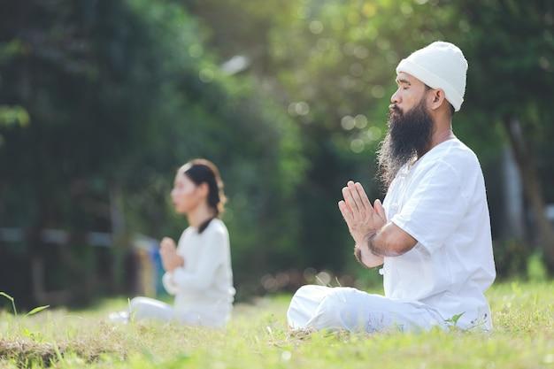 Dos personas en traje blanco meditando en la naturaleza Foto gratis