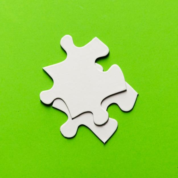 Dos piezas del rompecabezas blanco sobre fondo verde brillante Foto gratis