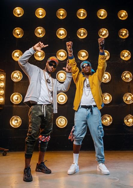Dos raperos negros en mayúsculas, actuando en el escenario con focos en la pared. artistas de rap en escena con luces, concierto de música underground, estilo urbano Foto Premium