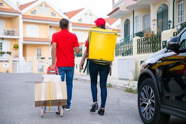 Dos repartidores caminando y buscando dirección. vista posterior de mensajeros adultos que entregan el pedido en bolsa térmica y cajas de cartón en carro. servicio de entrega, concepto de correo y envío. Foto gratis