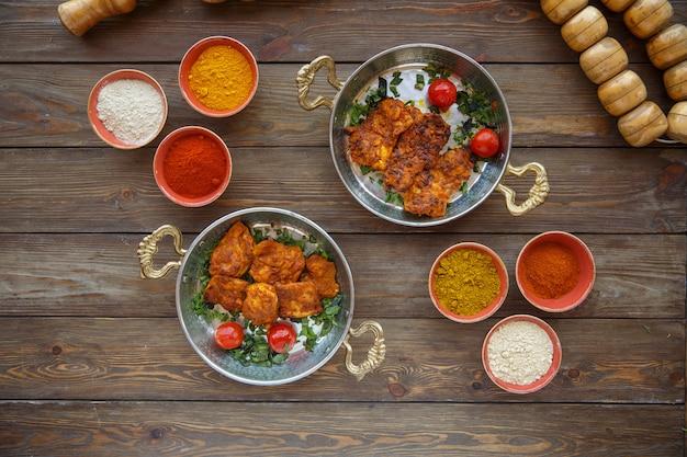 Dos sartenes cobrizos con pollo marinado adornado con tomates y hierbas Foto gratis