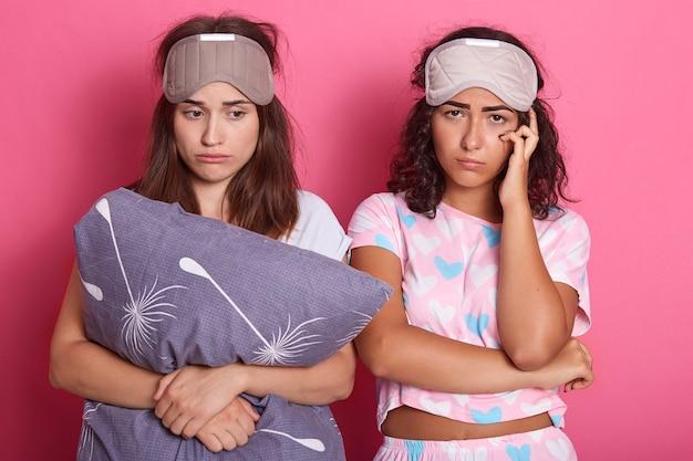 Dos señoras soñolientas de pelo oscuro con antifaz para dormir en la frente Foto Premium