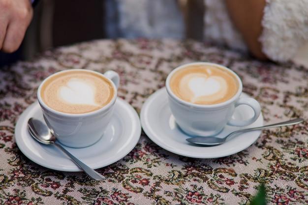 Dos Tazas De Café Con Leche Están Sobre La Mesa