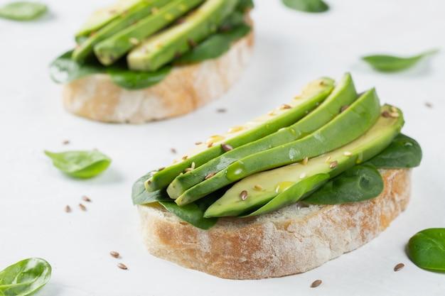 Dos tostadas ciabatta con aceite de oliva en rodajas de aguacate Foto Premium
