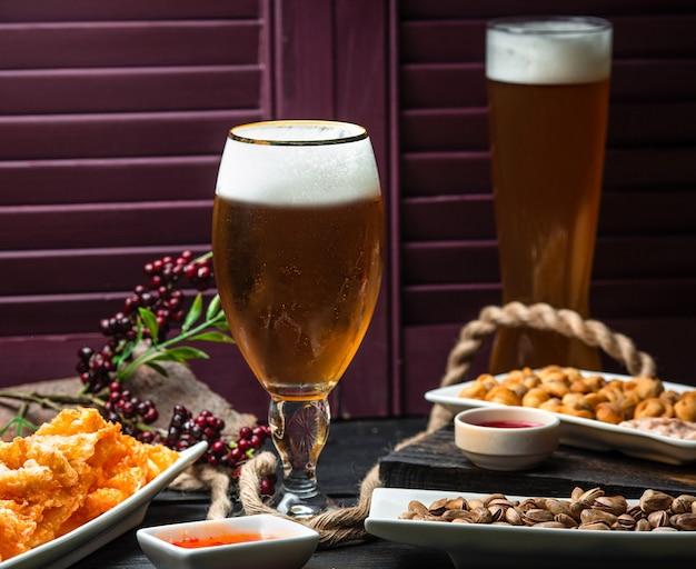 Dos vasos de cerveza servidos con pepitas, salsa de chile dulce y frutos secos. Foto gratis