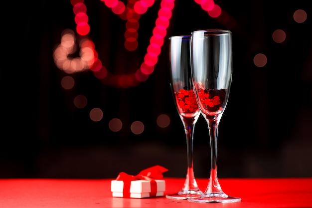 Dos vasos de corazones rojos. junto a ellos yace un regalo. concepto de san valentín Foto Premium