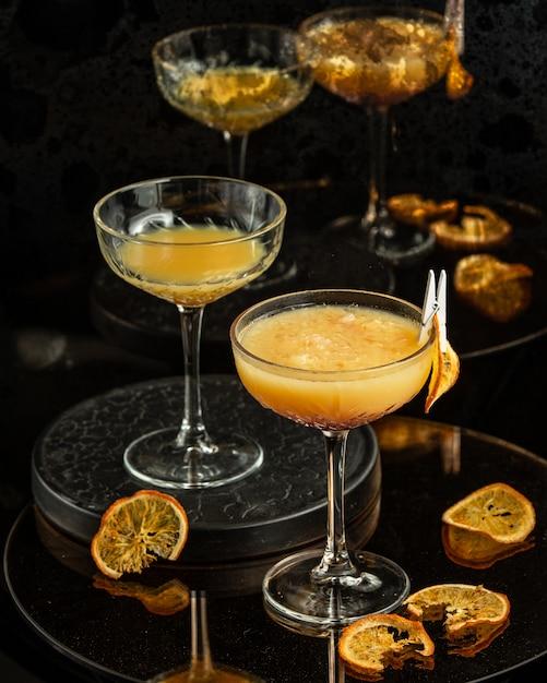 Dos vasos con tallo largo de cóctel de naranja con pulpa Foto gratis