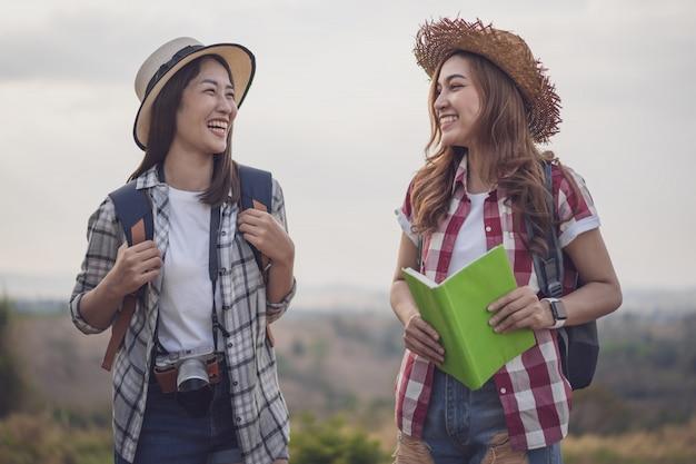 Dos viajeros mujeres alegres en el campo Foto Premium