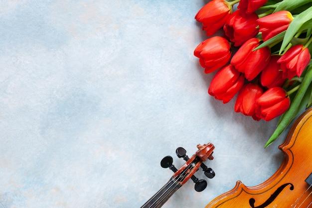 Dos viejos violines y ramo de tulipanes rojos. día de san valentín Foto Premium