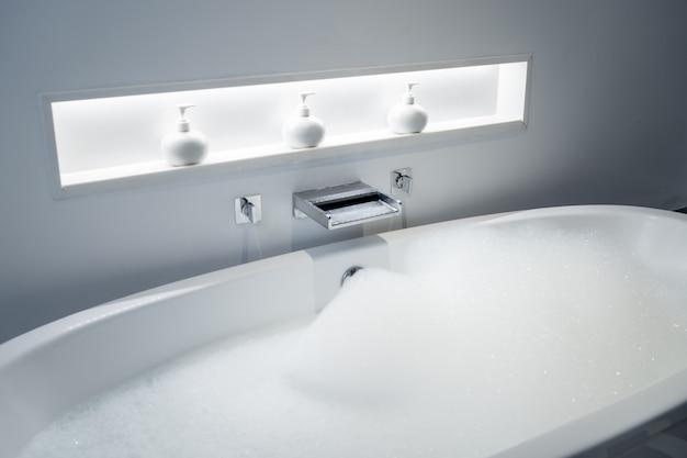 Ducharse en la bañera y jugar a pompas de jabón en el baño. Foto Premium