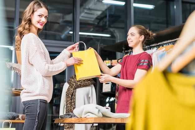 Dueño de la boutique dando una bolsa de papel amarilla a una joven sonriente Foto gratis