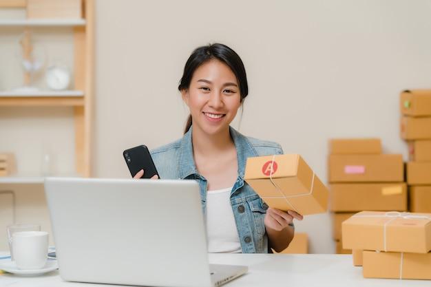Dueño joven asiático elegante hermoso de la mujer de negocios del empresario de la pyme que comprueba el producto en el código común del qr de la exploración que trabaja en casa. Foto gratis