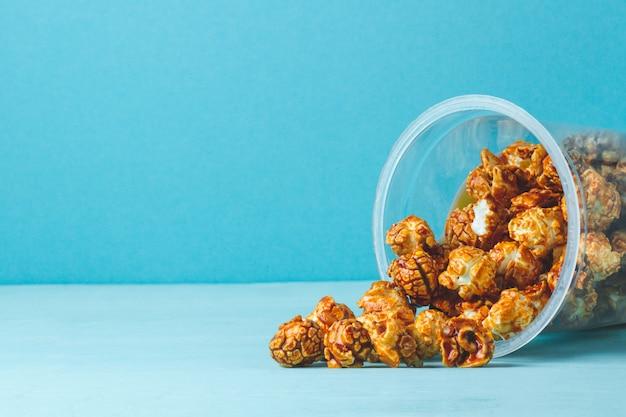 Dulce, caramelo de palomitas de maíz sobre un fondo azul. copia espacio Foto Premium