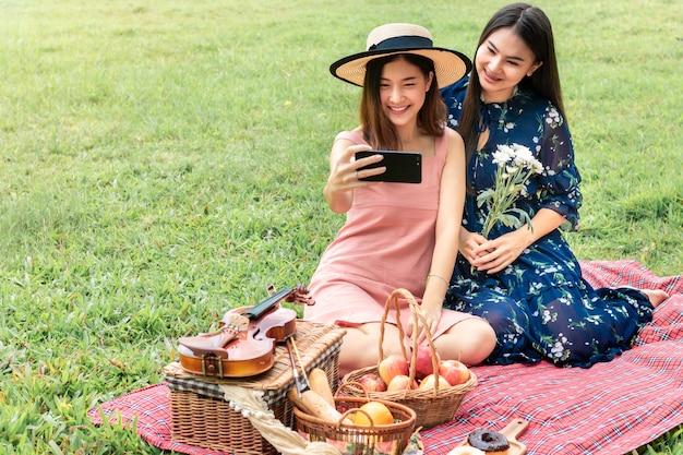Dulce momento de amor. retrato de pareja homosexual asiática divertida selfie y picnic en el parque. concepto lgbt leasbian. Foto Premium