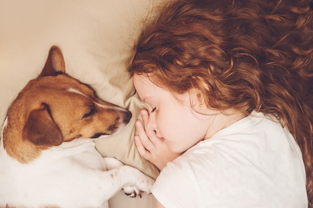 Dulce niña rizada y el perro está durmiendo en la noche. Foto Premium