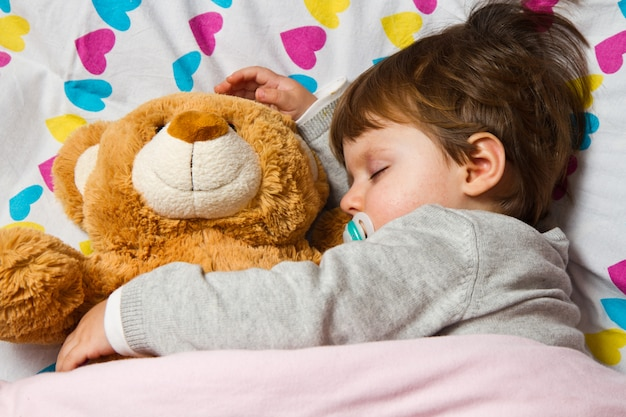 Dulce niño durmiendo con osito de peluche. Foto Premium