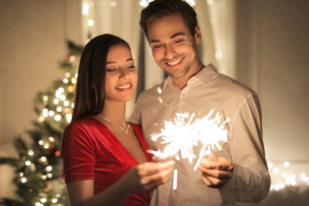 Dulce pareja abrazados en casa, celebrando la víspera de navidad Foto Premium