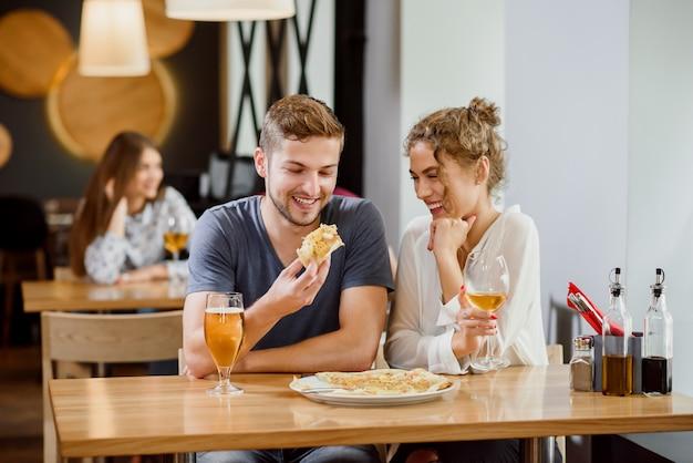 Dulce pareja comiendo pizza y bebiendo cerveza y vino en pizzería. Foto Premium