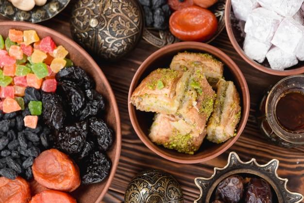 Dulces árabes para el baklava del ramadán; lukum y frutas secas en un tazón sobre el escritorio Foto gratis