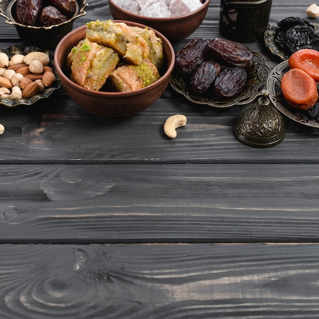 Dulces de baklava delicias turcas; frutos secos y nueces en escritorio de madera Foto gratis