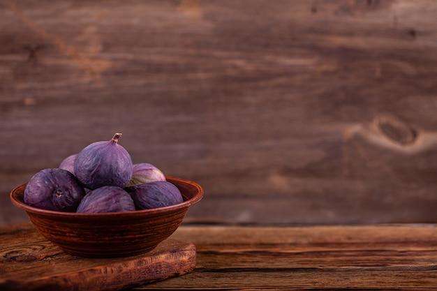 Dulces higos violetas maduras en un tazón vintage, mesa de madera, concepto de dulces veganos Foto Premium