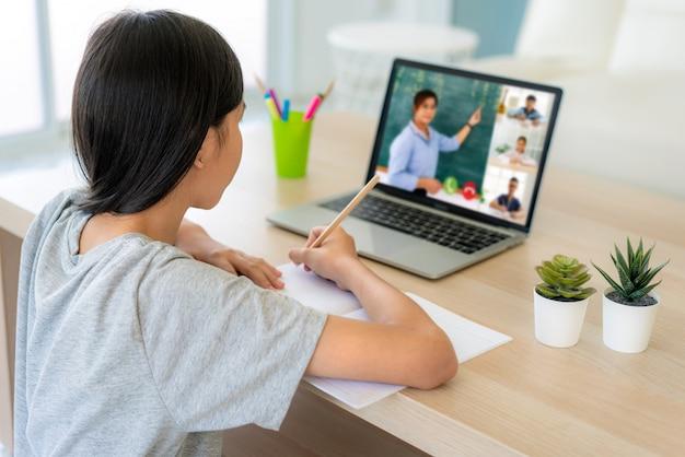 E-learning de videoconferencia de una estudiante asiática con maestra y compañeros de clase en la computadora en la sala de estar en casa Foto Premium